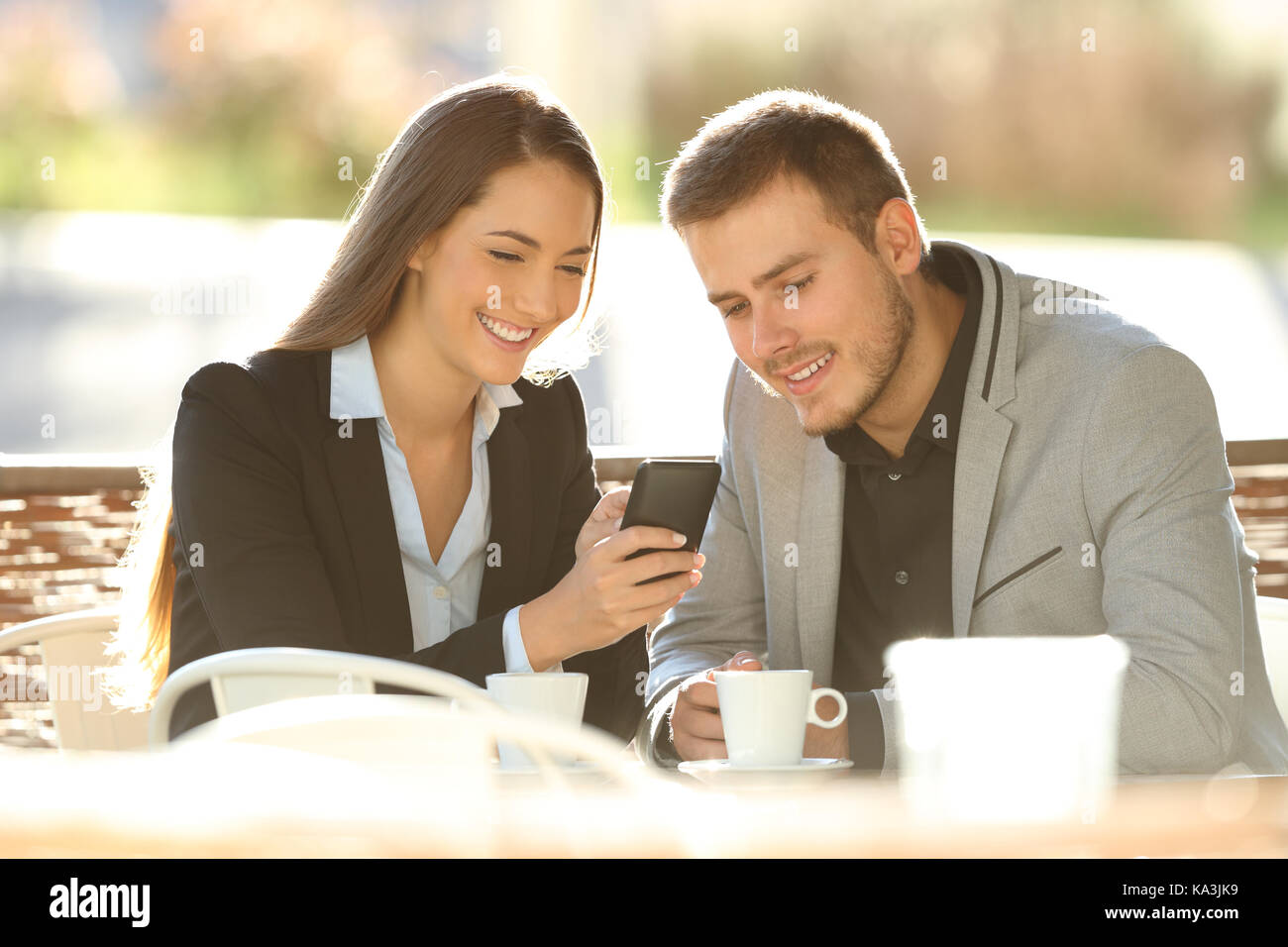 Two happy executives using a smart phone sitting in a restaurant terrace with a warm light in the background - Stock Image