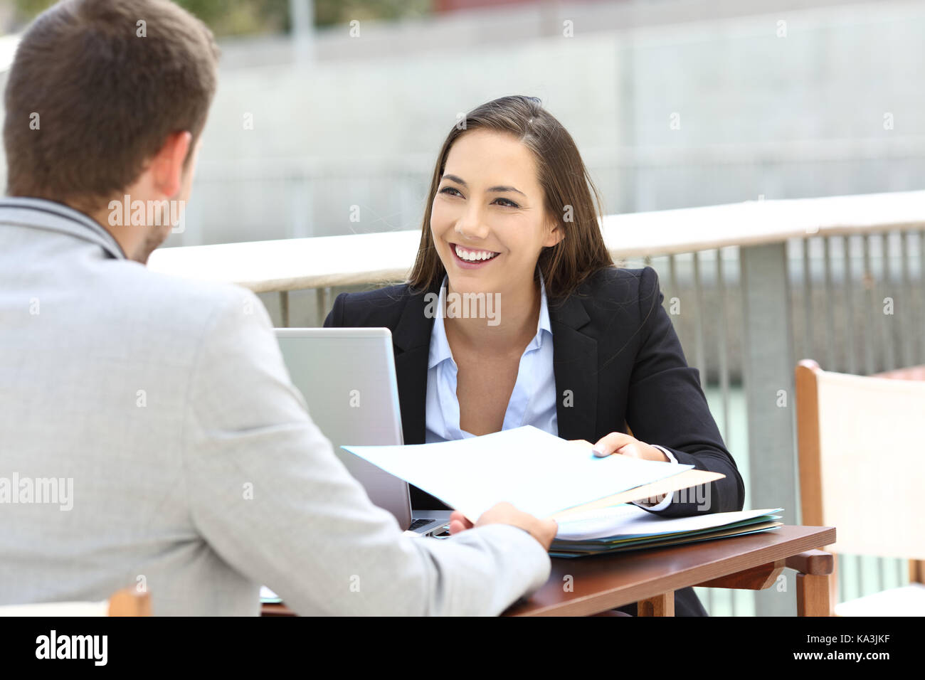 Two executives working sharing informs sitting in a bar terrace - Stock Image