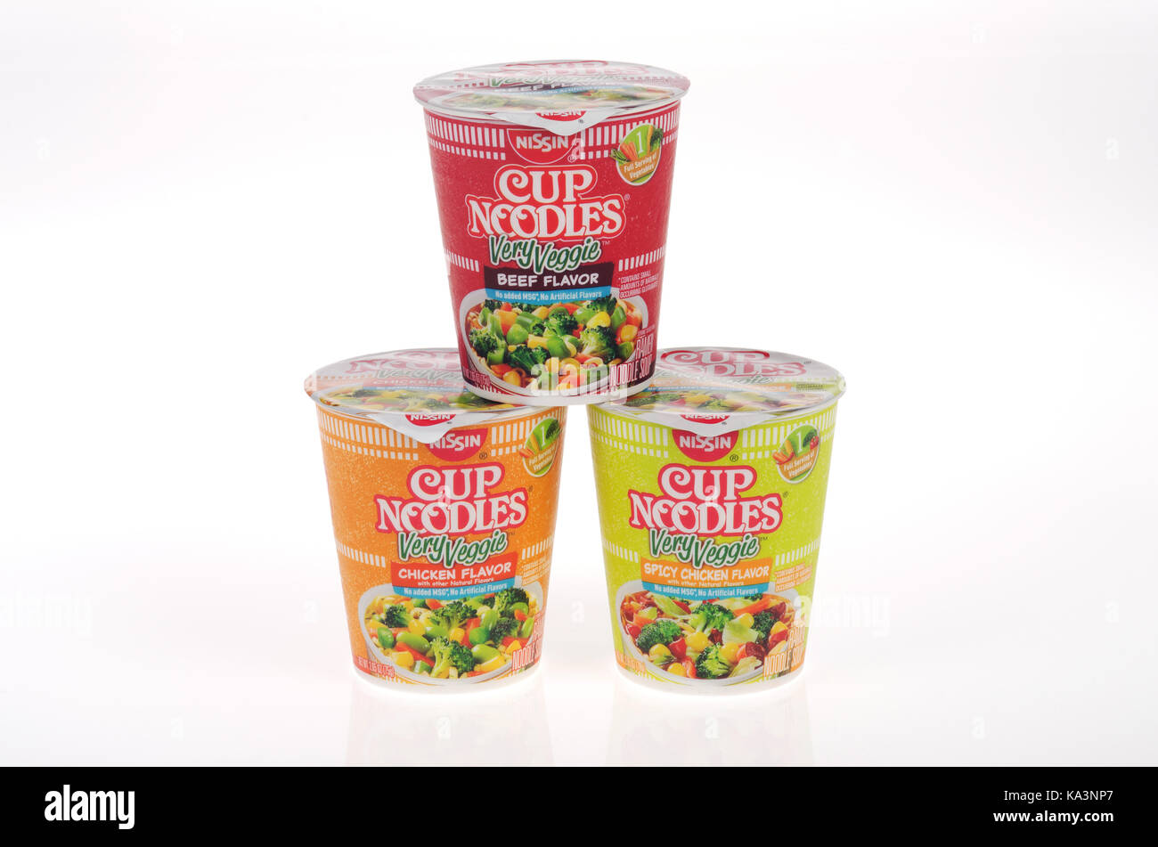 Nissin Cup of Noodles Very Veggie Flavors chicken, spicy chicken and beef in unopened containers stacked on white - Stock Image
