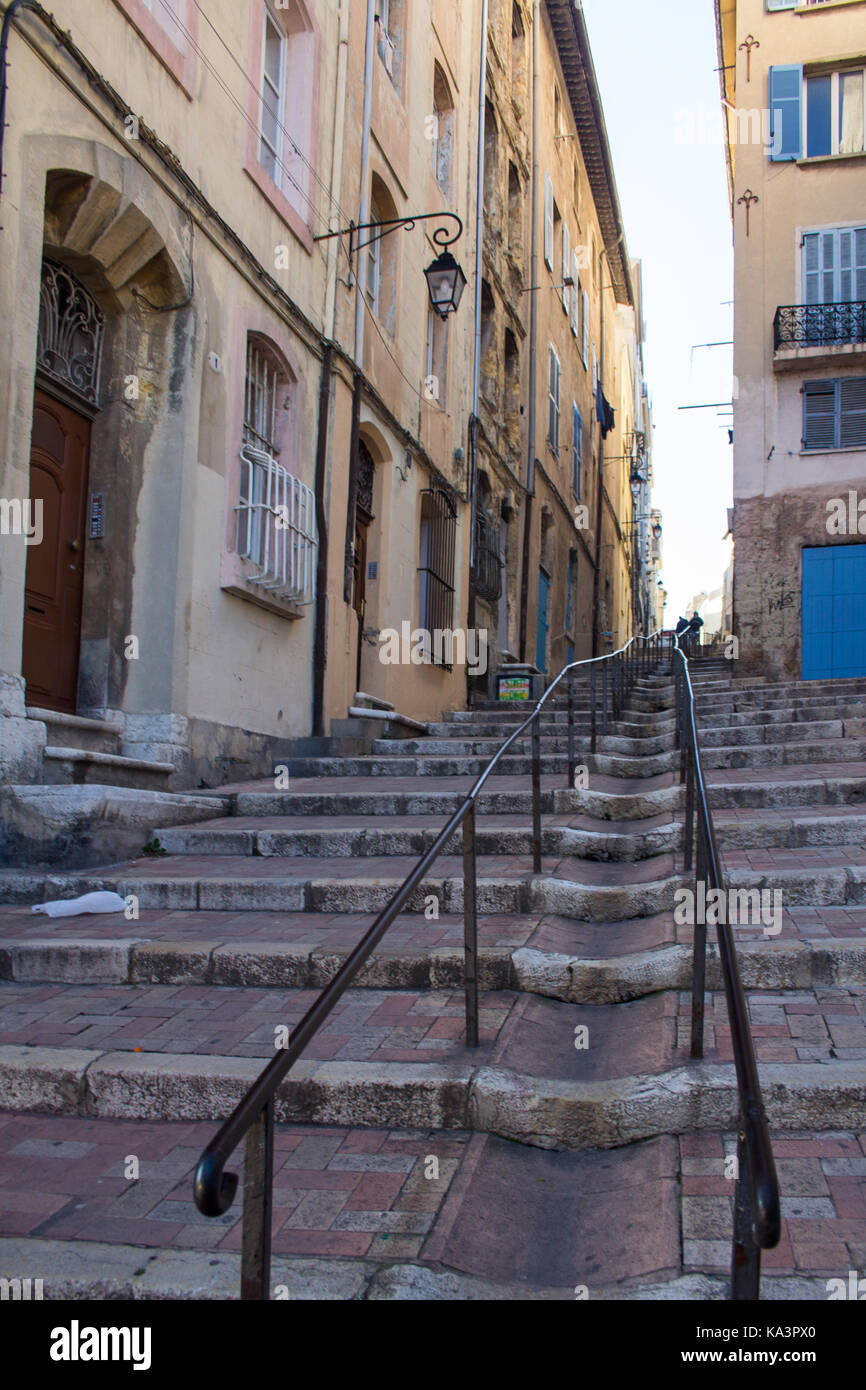 Steep pedestrian street in Marseille, France. Hand rails and steps lead a long way up. - Stock Image