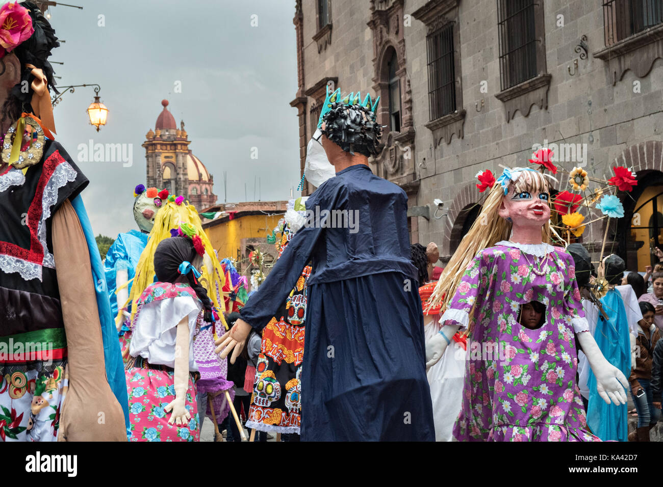 A parade of giant paper mache puppets called mojigangas dance in a procession through the city at the start of the - Stock Image