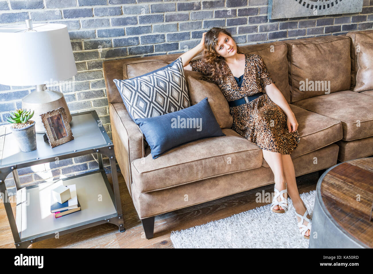 Remarkable Brown Leather Sofa Woman Happy Stock Photos Brown Leather Dailytribune Chair Design For Home Dailytribuneorg
