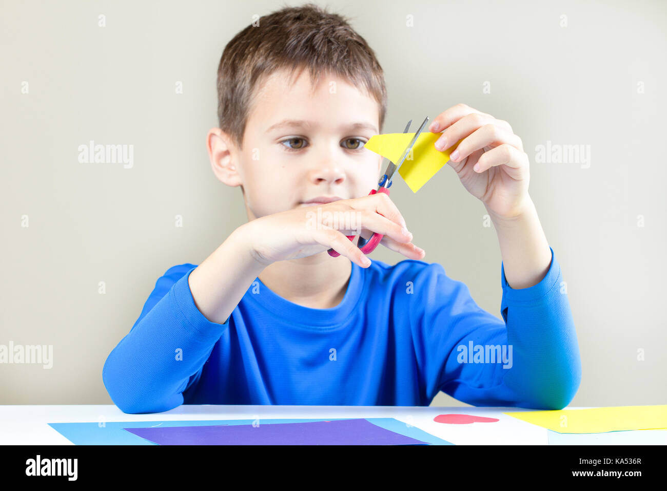Boy cutting colored paper with scissors at the table - Stock Image