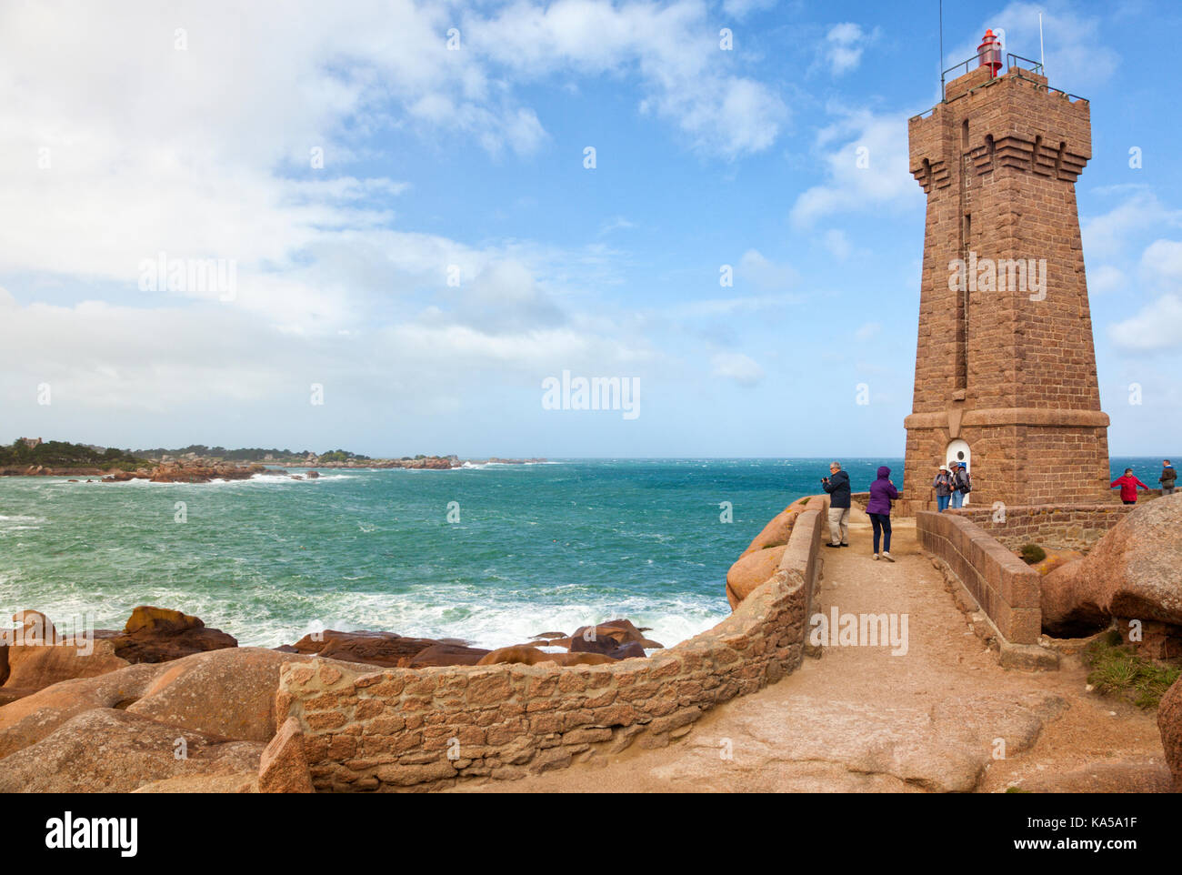 People visiting the lighthouse of Ploumanac'h at the french Côte de granite rose in Brittany - Stock Image