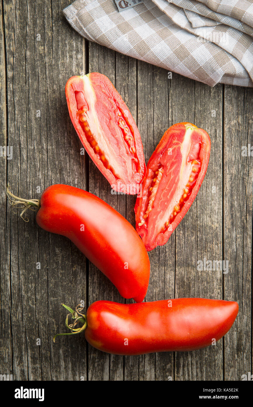 Halved San marzano tomatoes on old wooden table. Top view - Stock Image