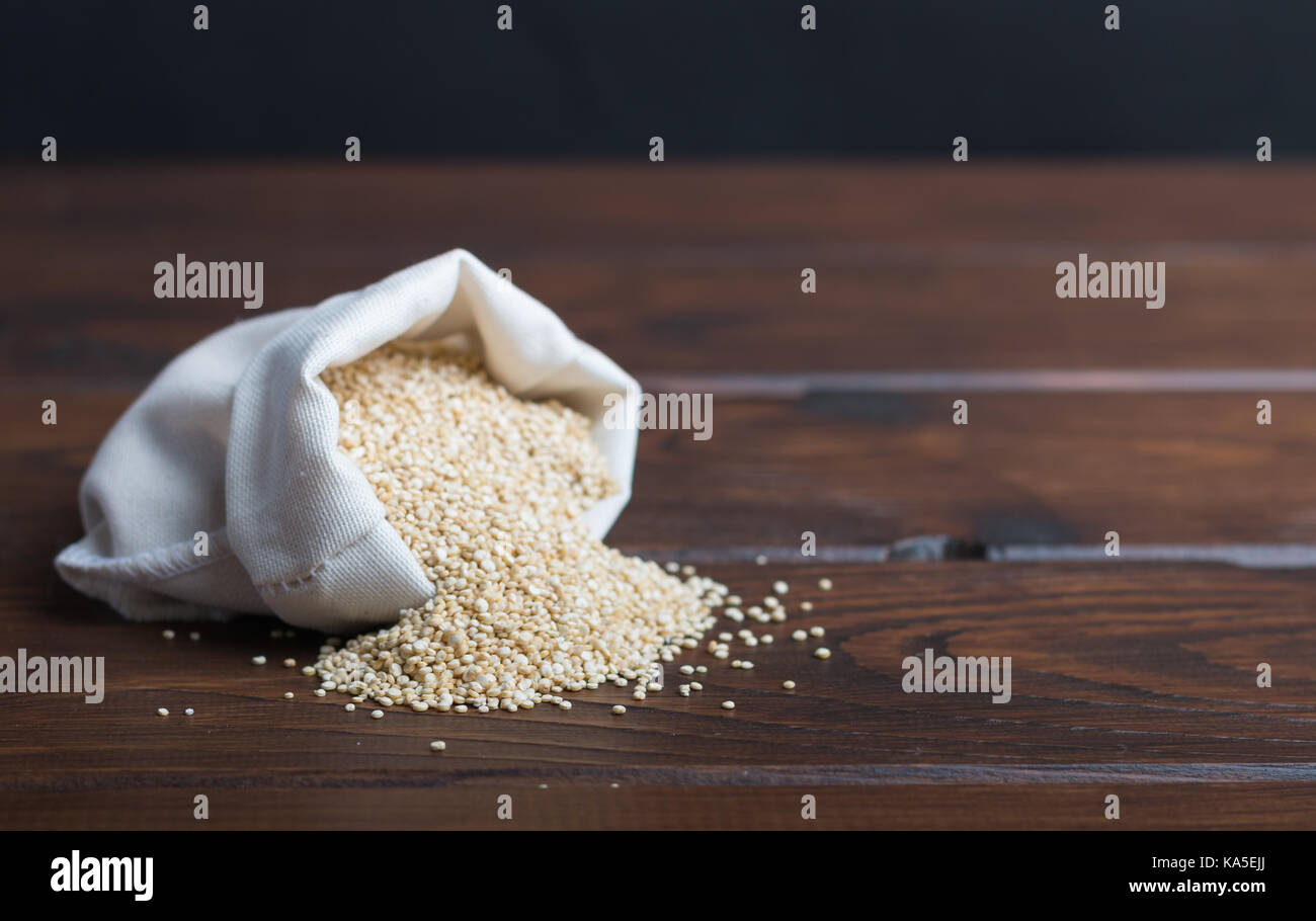 sac of bio quinoa on a wooden table - Stock Image