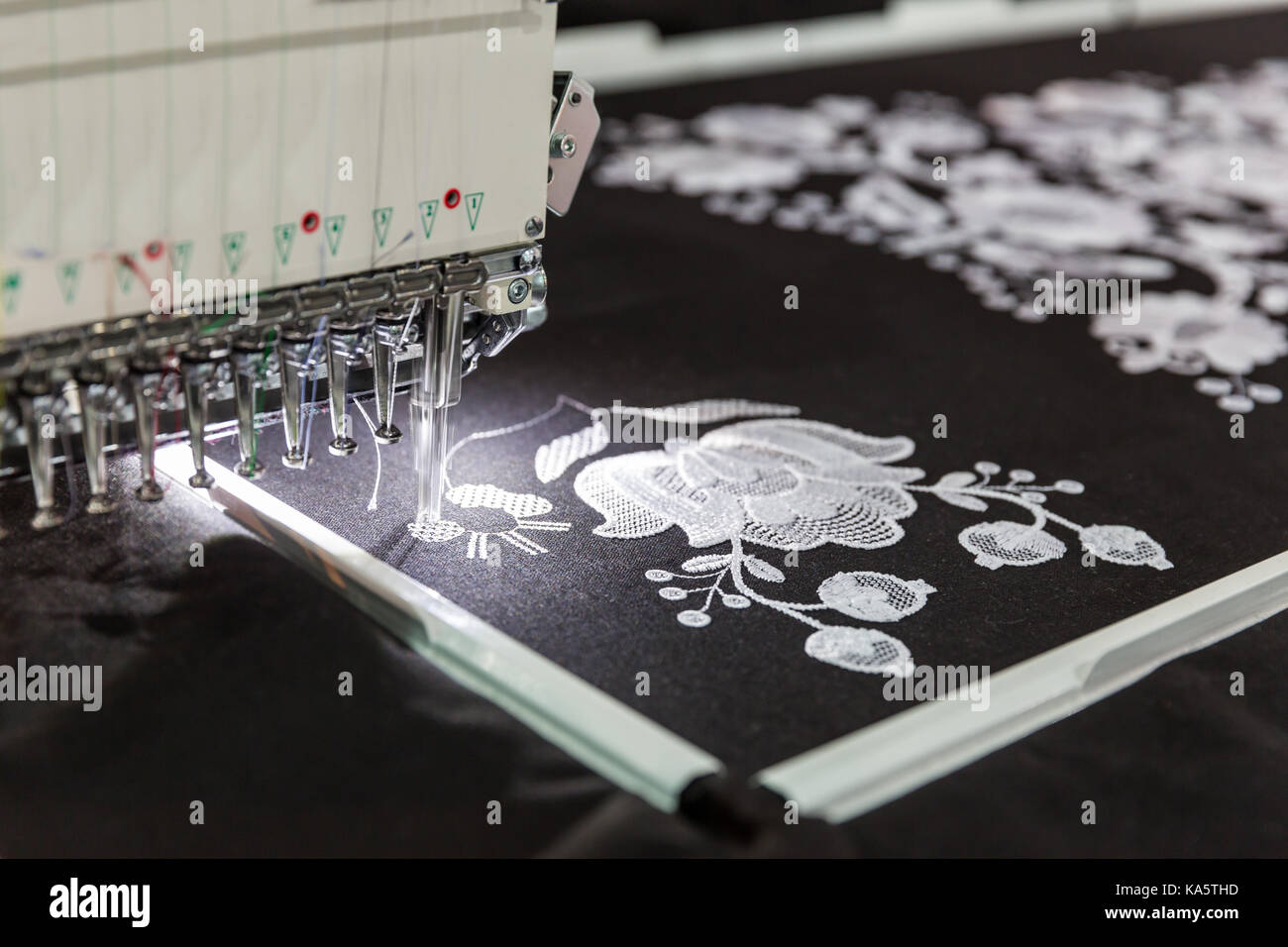 Sewing machine in work, textile fabric, nobody. Factory production, sew manufacturing, needlework technology Stock Photo