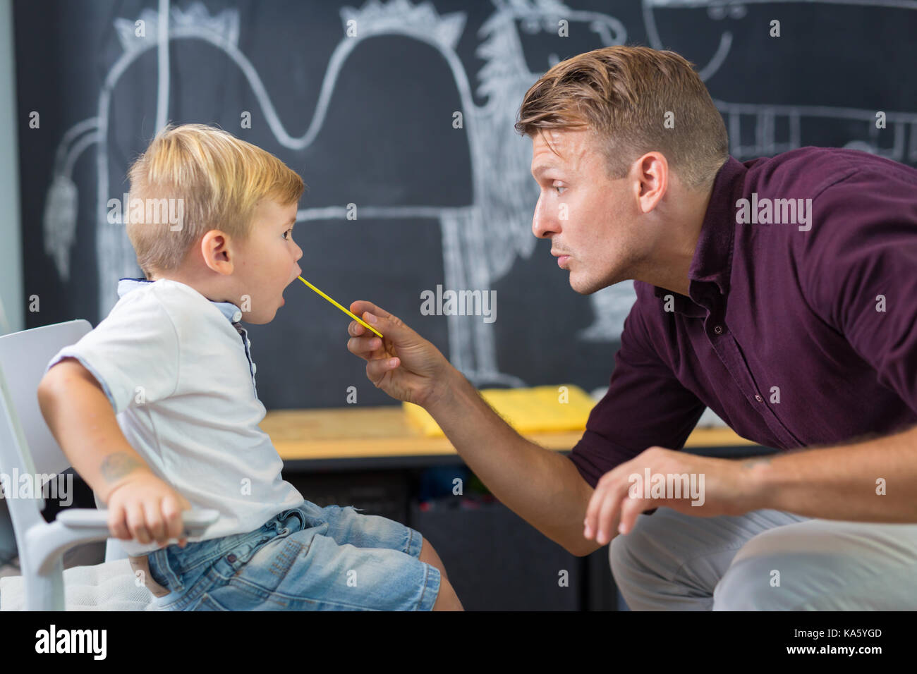 Cute little boy at speechtherapist session. - Stock Image