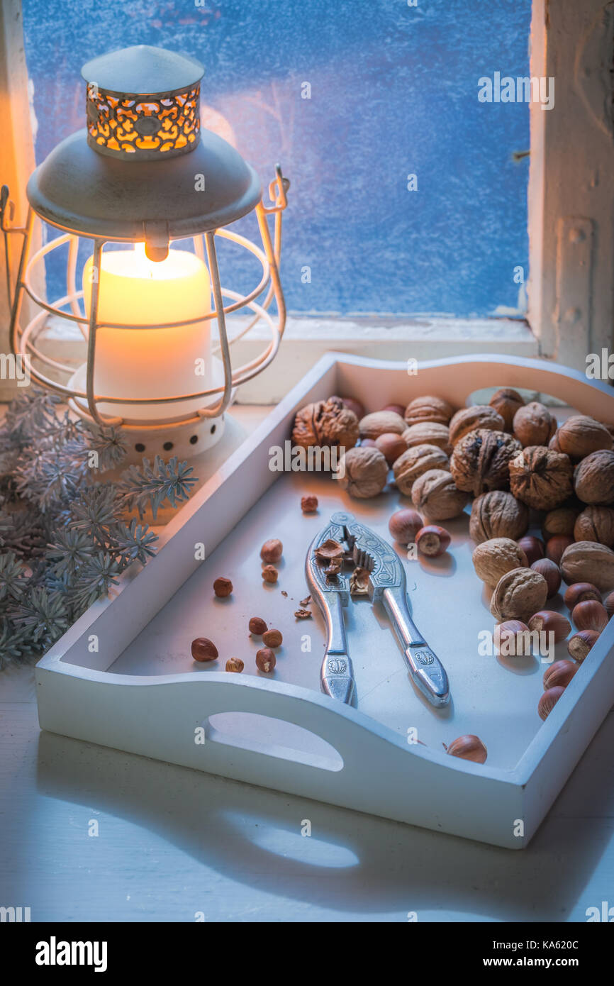 Nuts with nutcrackers for Christmas and cold window - Stock Image