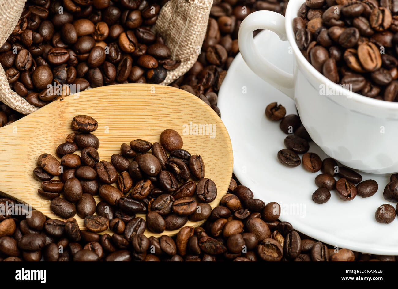 Coffee beans in jute sack  with wooden spoon and espresso cup. Top view - Stock Image