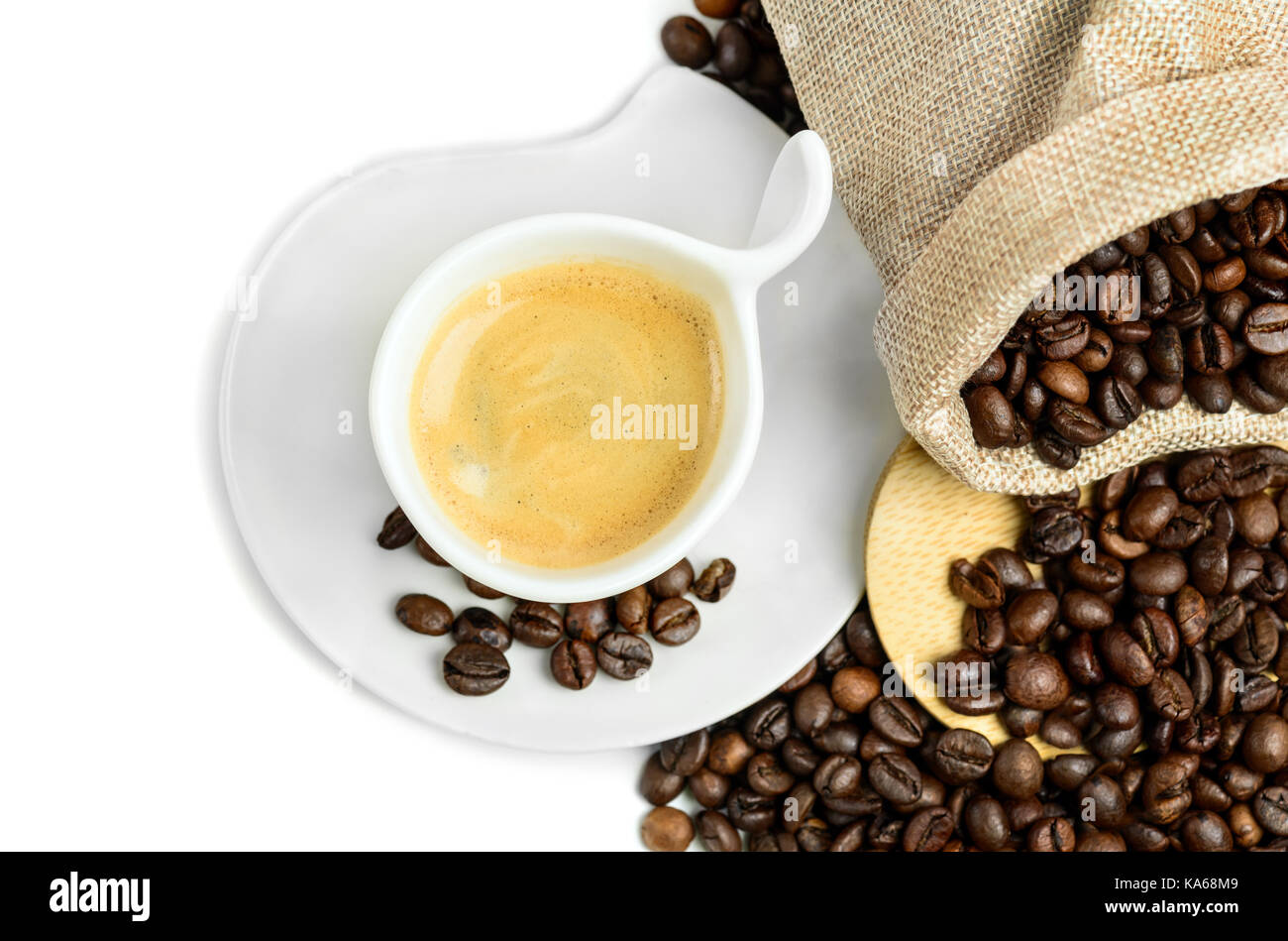Coffee cup and beans on a white background. Top view. Focus on foam. - Stock Image