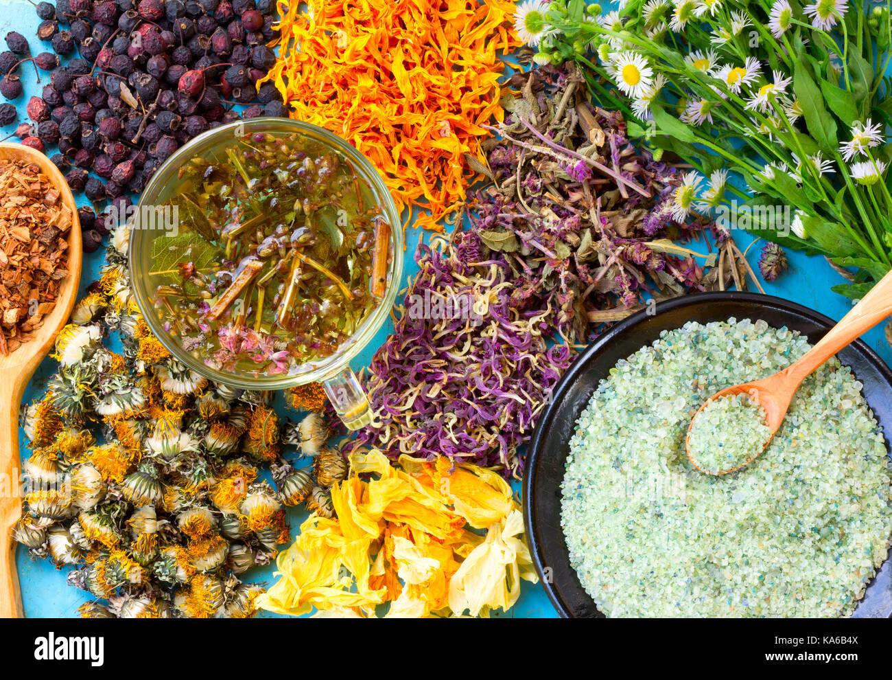 Hot herbal tea, a set of dried flowers and berries, herbs, oak bark, sea salt on old wooden table. Alternative medicine, Stock Photo