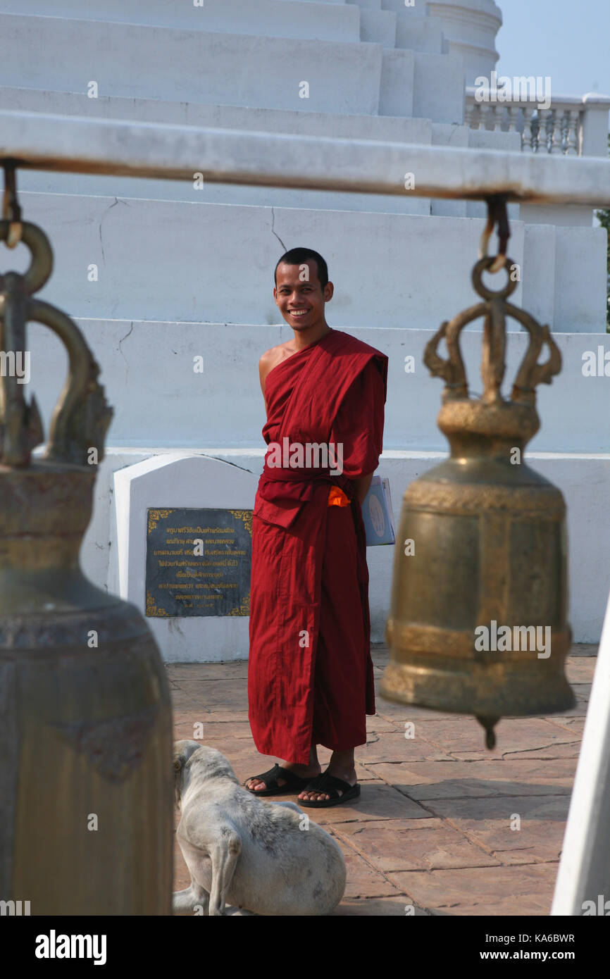 Daily life in a Buddhist monastery. Young cheerful smiling monk in a monastery near the sacred bell. - Stock Image