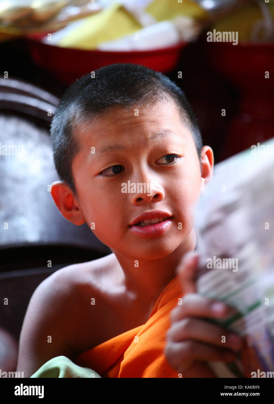 Daily life in a Buddhist monastery. Closeup portrait of a little smiling boy -  Buddhist monk in a monastery. - Stock Image