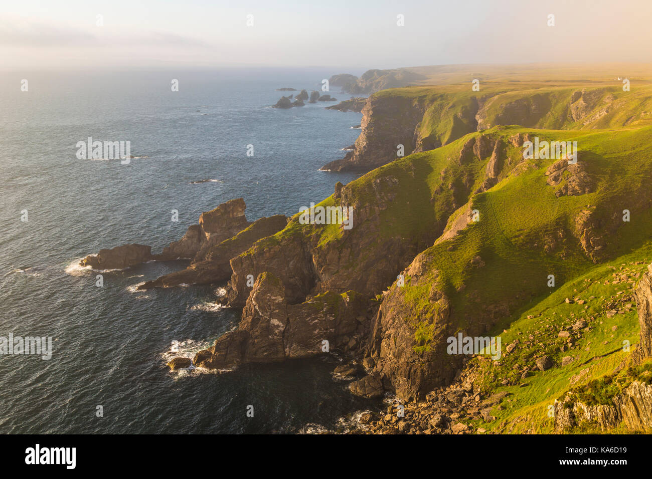 Mull of Oa, Islay, Scotland, in evening time with nice warm light, fog is comming in over the cliffs, gren grass - Stock Image