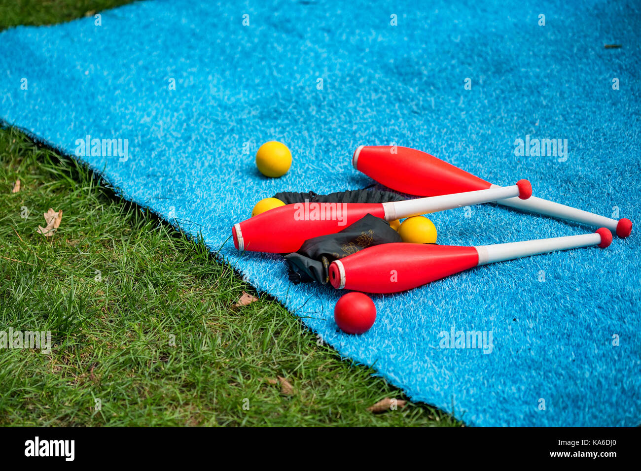 Juggling clubs and balls on lie blue mat close-up - Stock Image