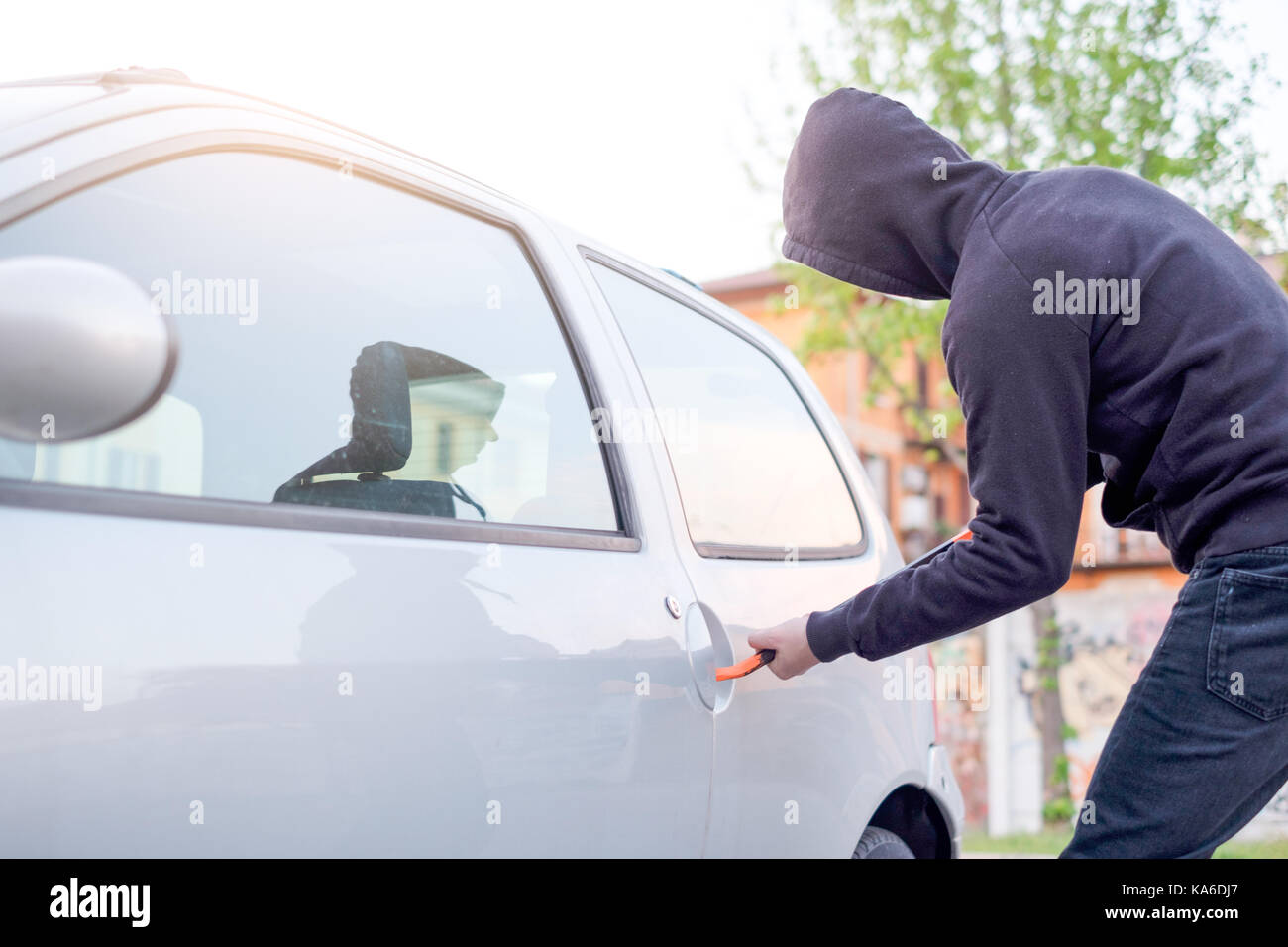 Thief trying to pick the lock of a parked car - Stock Image