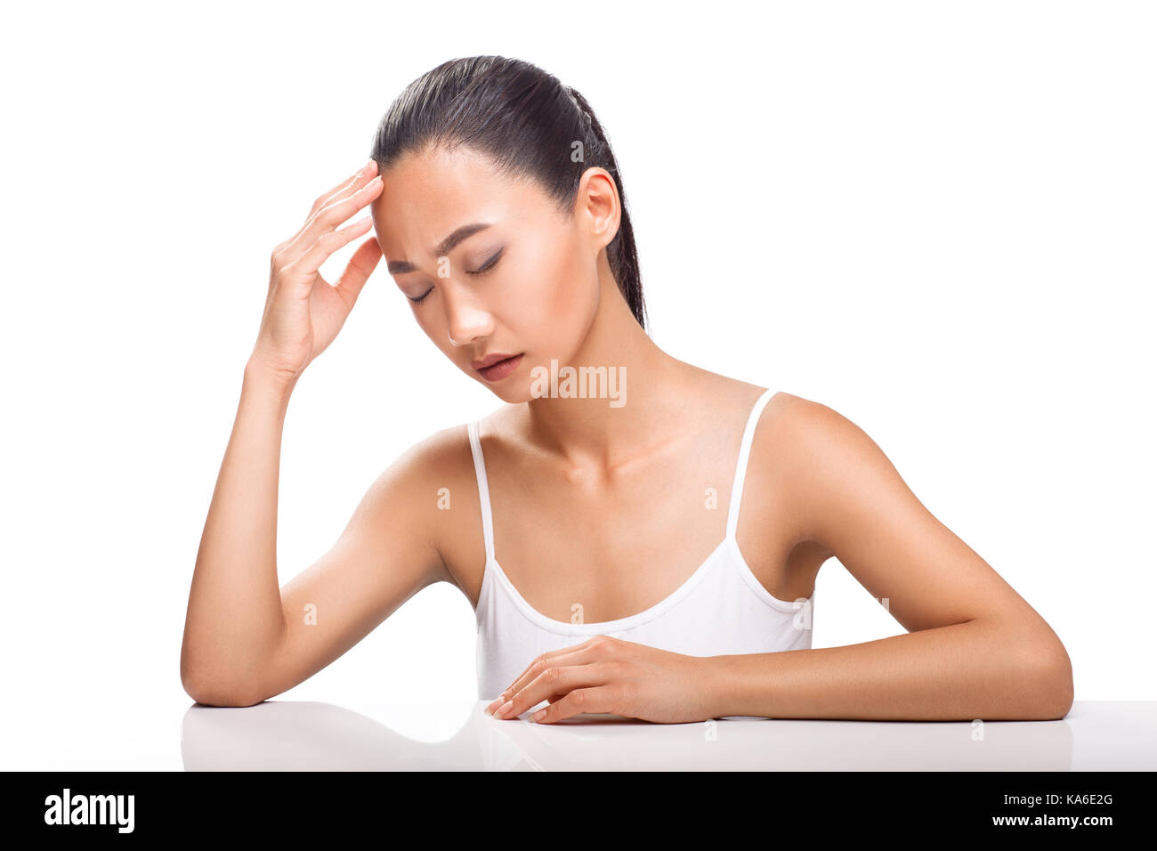 Young Asian woman having headache. Girl siting with sickly look and closed eyes. Expression of emotion pain, stress - Stock Image