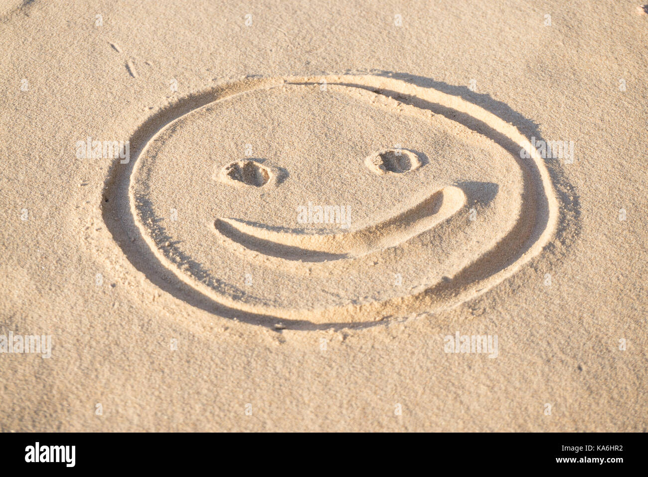 Prints of emoji smile in the sand on the beach of the Baltic Sea in summer: summer is almost gone, waiting for autumn. - Stock Image