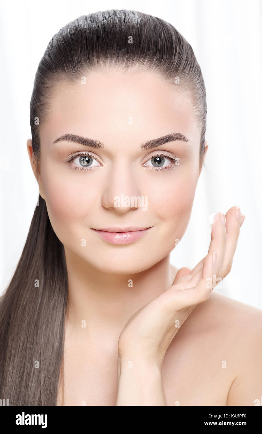 Young woman with cream. - Stock Image