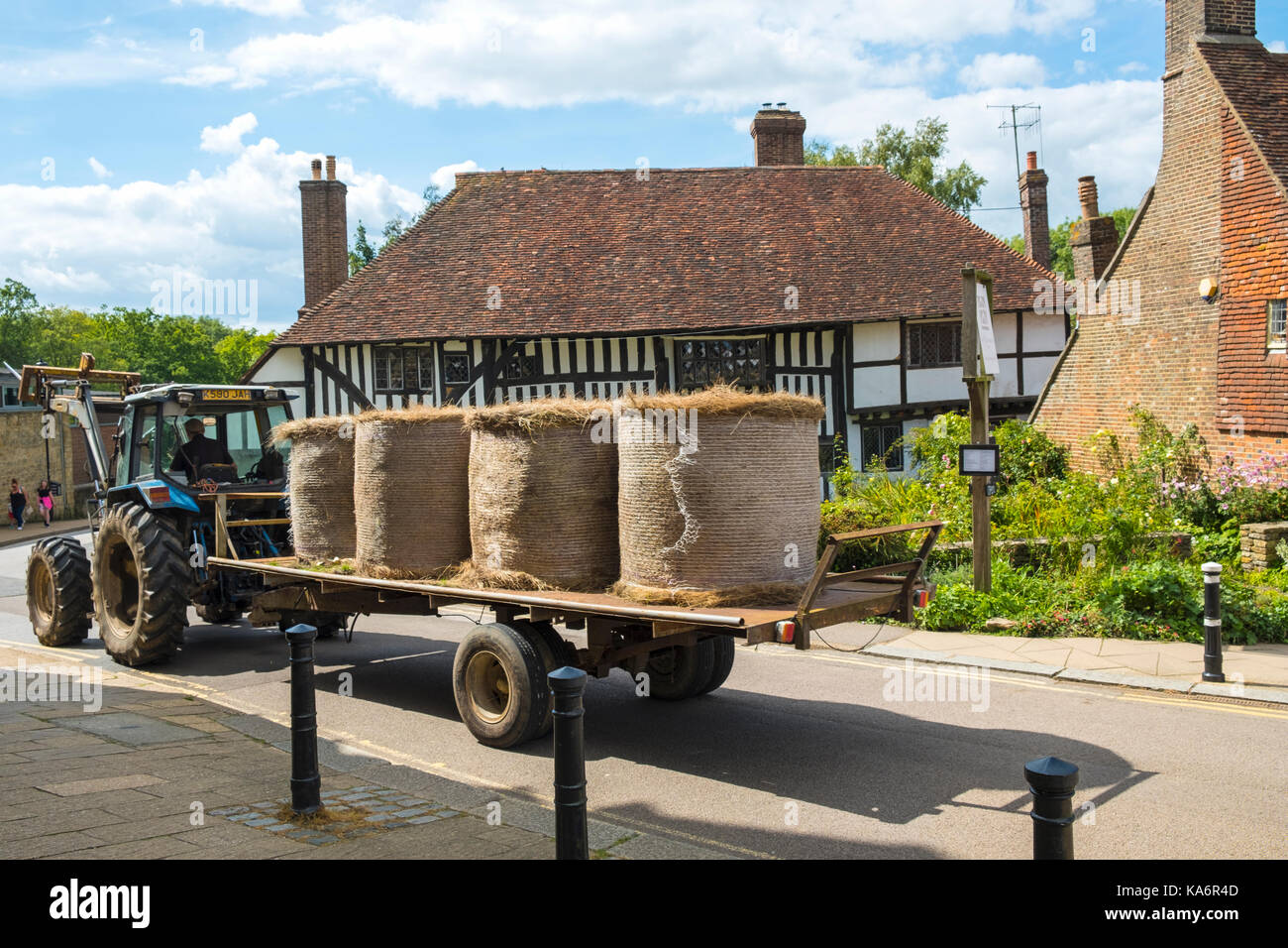 Straw bales on a tractor going to the farm through picturesque Battle Town, East Sussex, England, UK. - Stock Image