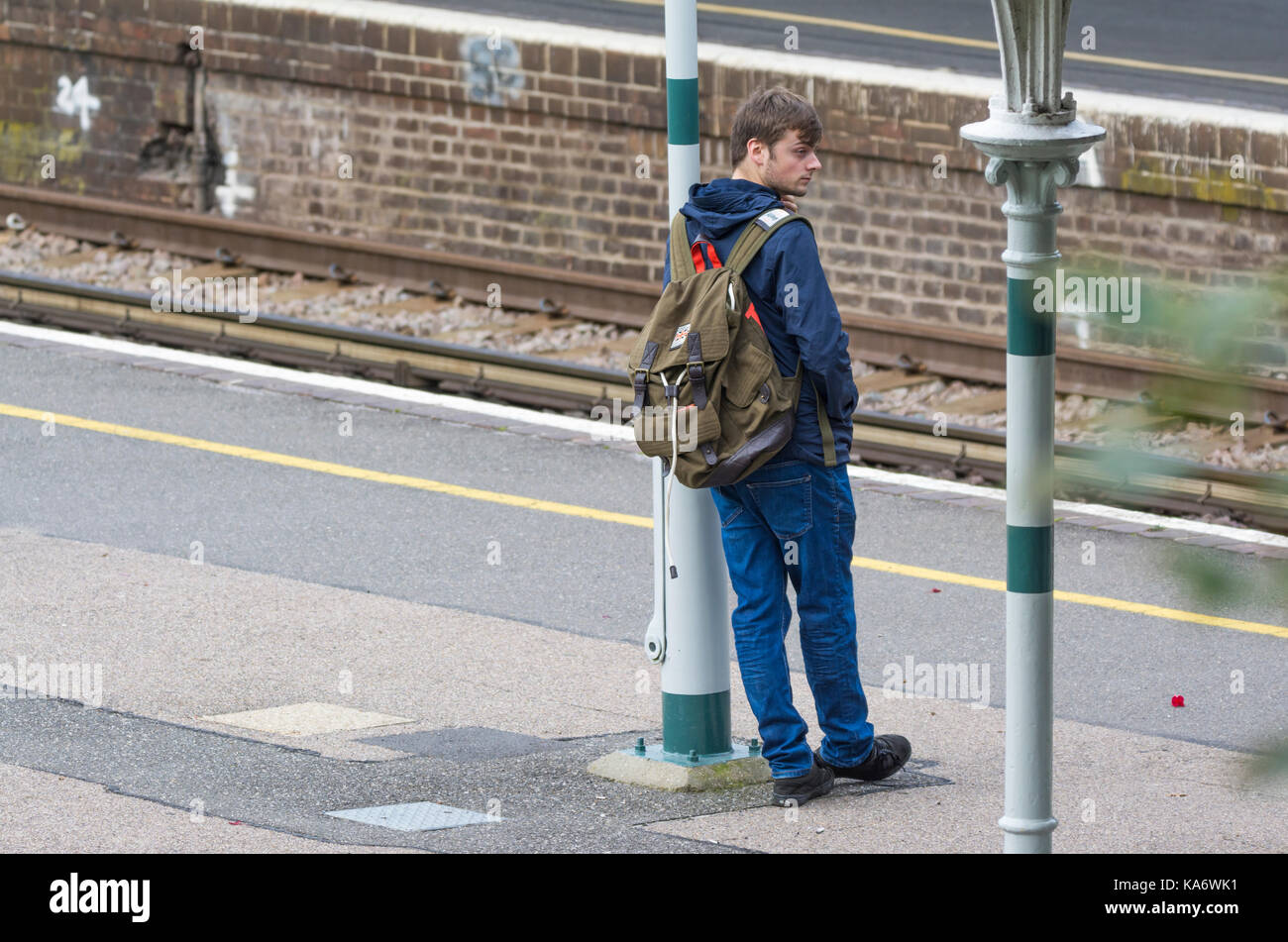 Man standing on a train platform waiting for a train at a British railway station in England, UK. - Stock Image