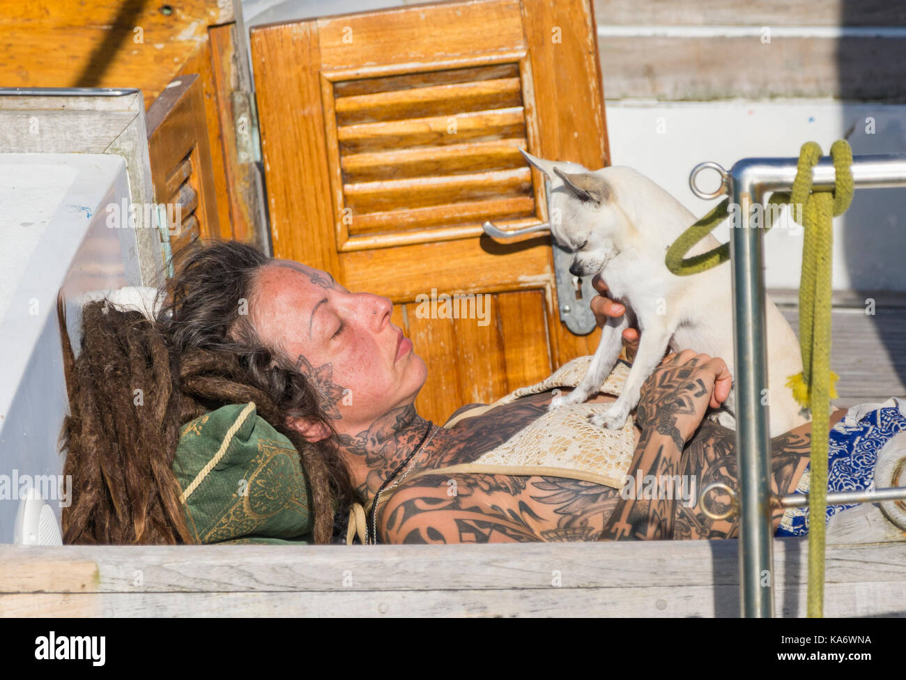 Woman with tattoos laying on a boat in the sun with a dog. - Stock Image