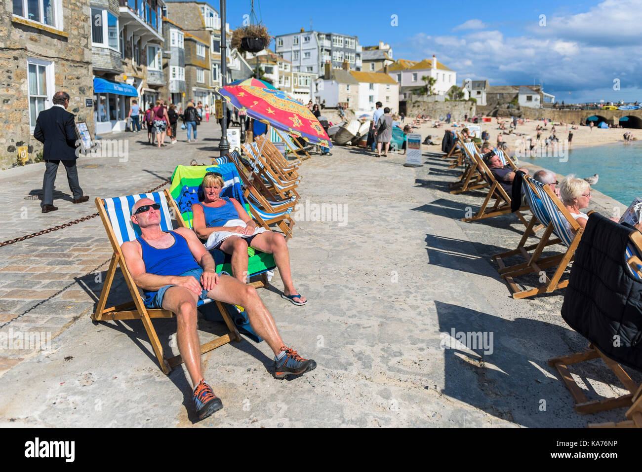 St Ives - holidaymakers relaxing in deckchairs on the quay at St Ives Harbour Beach Cornwall. - Stock Image