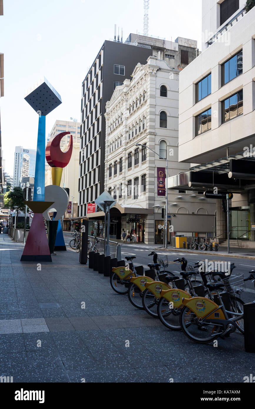 A row of parked hire bicycles and coloured sculptures on Albert Street in Brisbane, Queensland, Australia - Stock Image