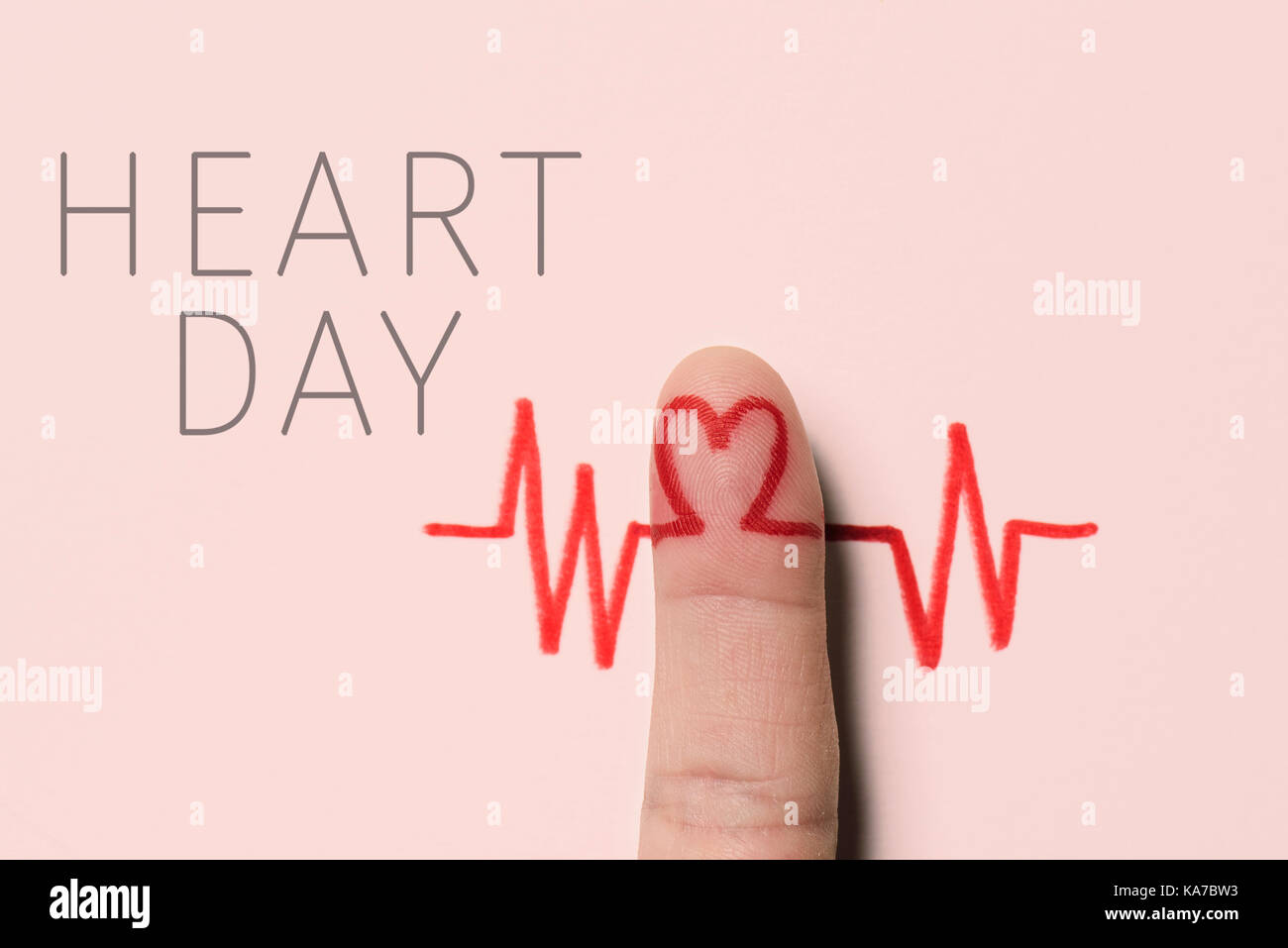 a red heart symbol in the forefinger of a man as in an electrocardiogram painted on a pink background and the text - Stock Image
