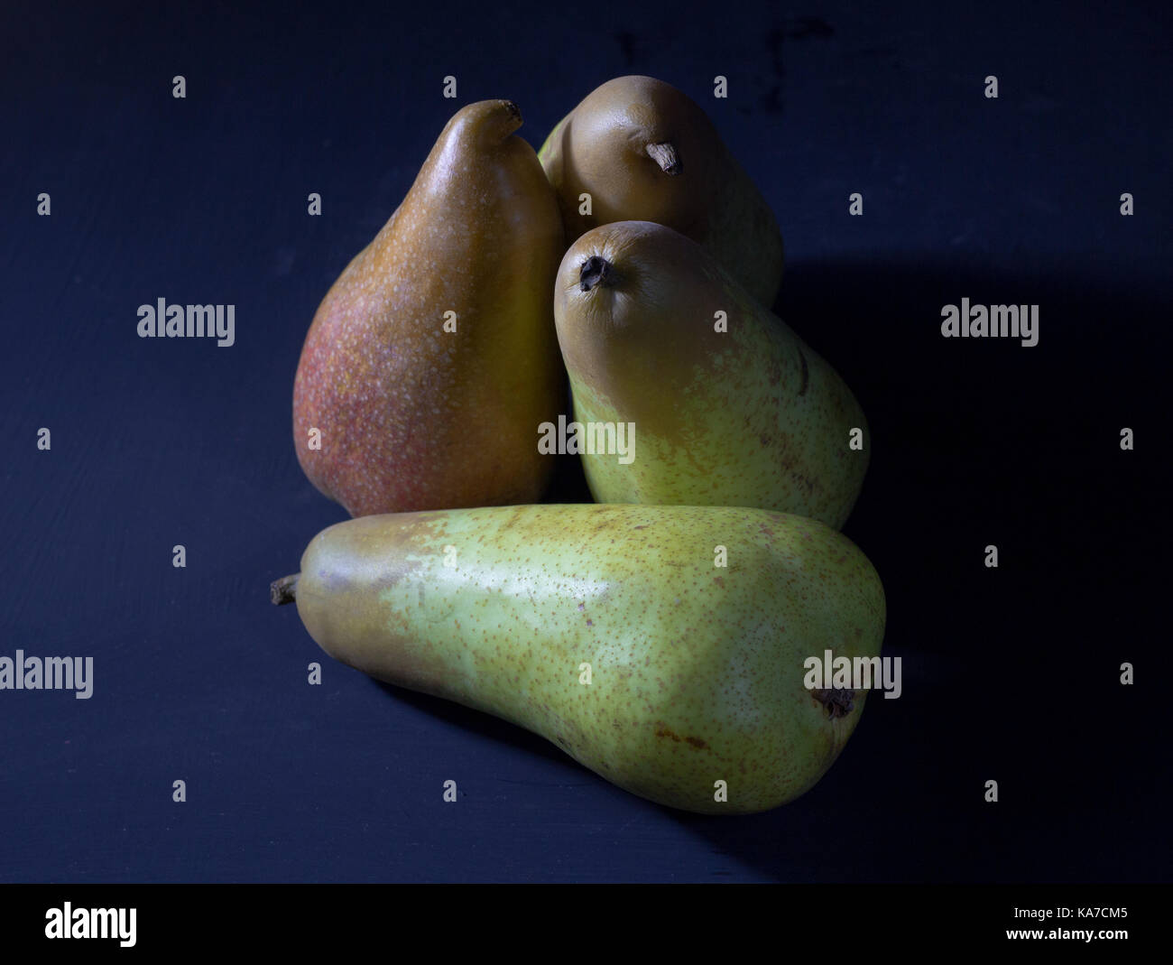 Pear fruit background with four fresh organic pears as unusual still life on dark blue background - Stock Image