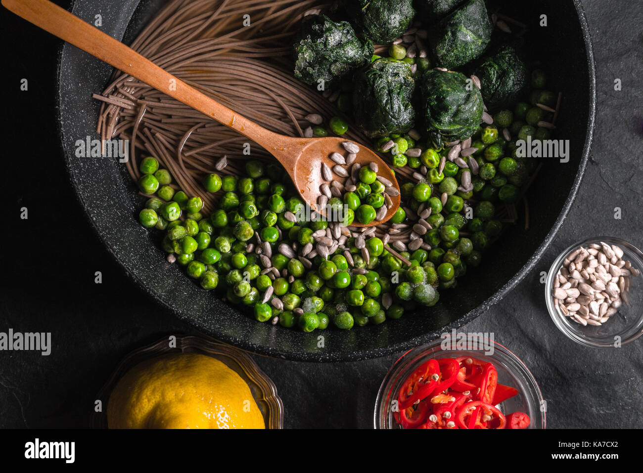 Buckwheat noodles in a frying pan, frozen peas and spinach, chillies and seeds in a bowl horizontal - Stock Image