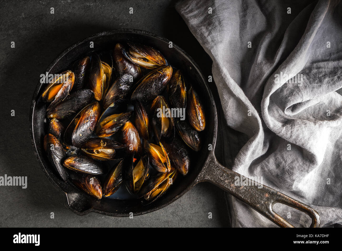 Mussels on a cast-iron frying pan and napkin on a gray background diagonal horizontal - Stock Image