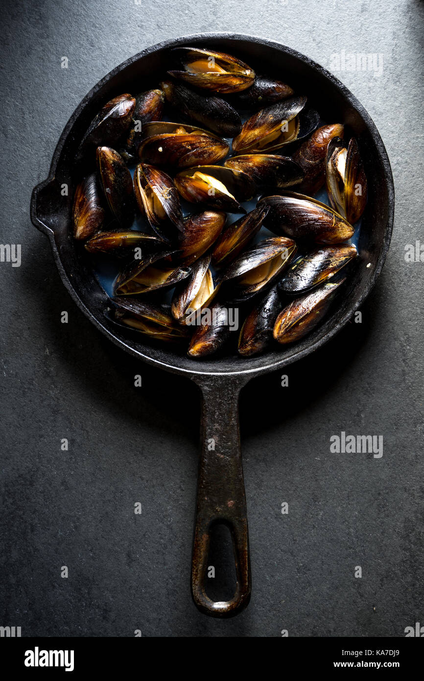 Mussels steamed on a cast-iron frying pan vertical Stock Photo