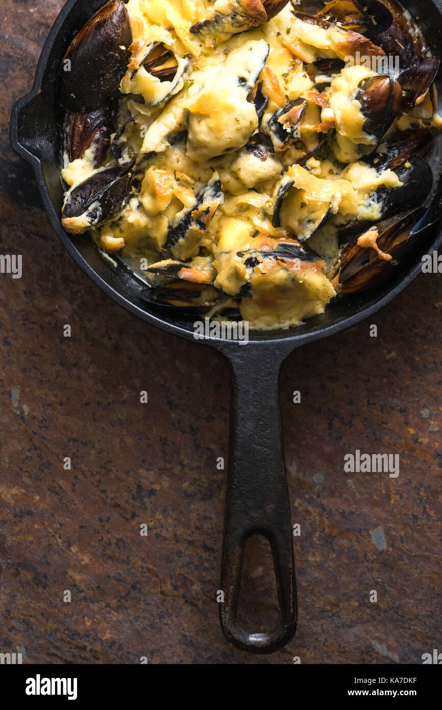 Frying pan with mussels under cheese sauce on a brown background vertical - Stock Image