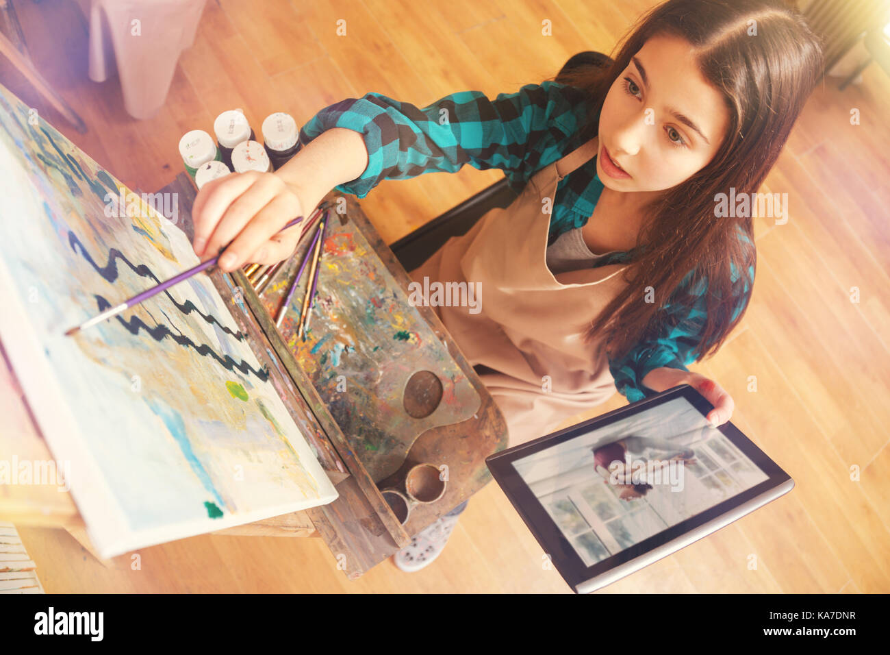 Charming girl painting abstract masterpiece on art canvas - Stock Image