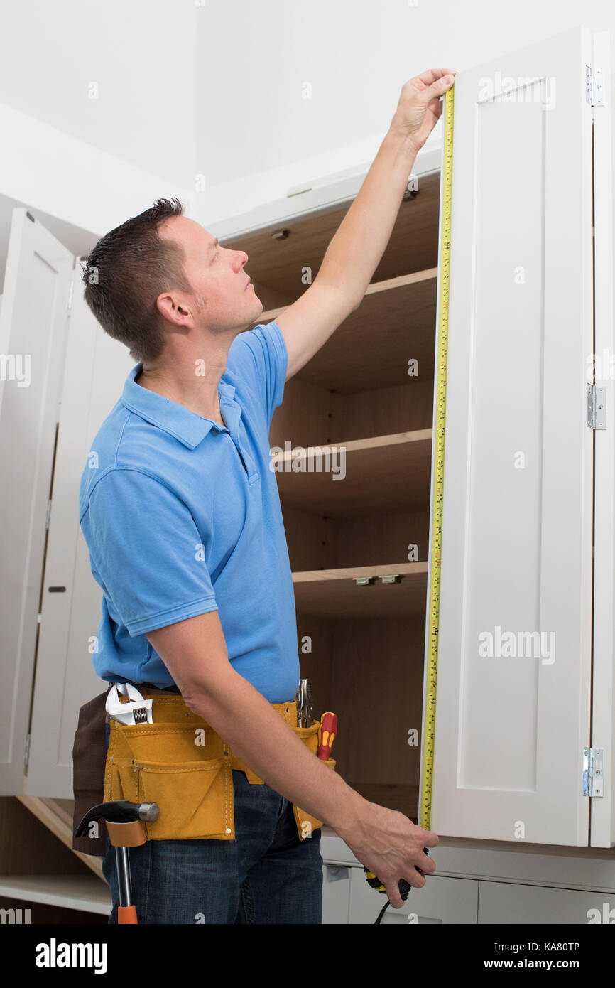 Carpenter Installing Luxury Fitted Kitchen - Stock Image