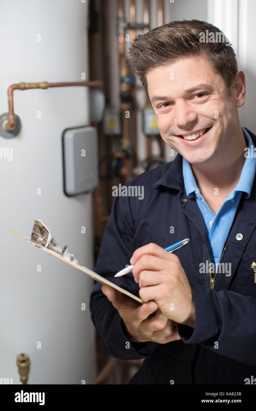 Male Plumber Working On Central Heating Boiler - Stock Image