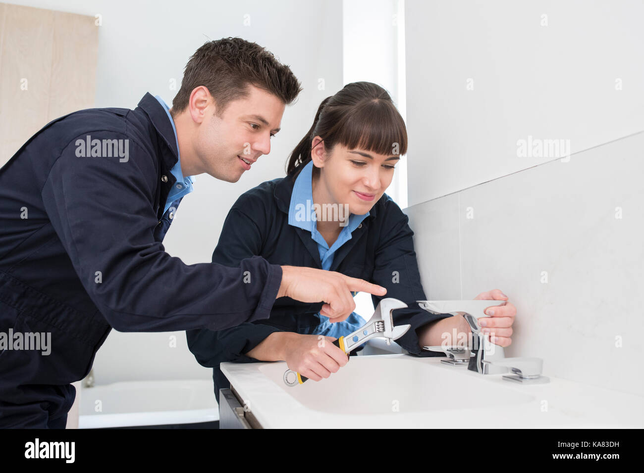 Female Trainee Plumber Working On Tap In Bathroom - Stock Image