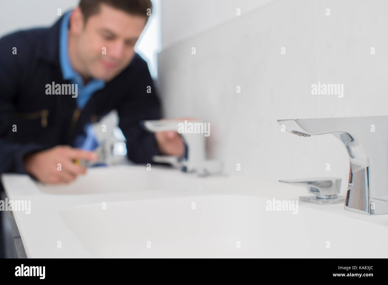 Plumber Working On Sink Using Wrench In Bathroom - Stock Image
