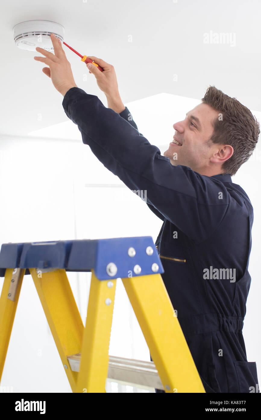 Man Installing Smoke Or Carbon Monoxide Detector - Stock Image