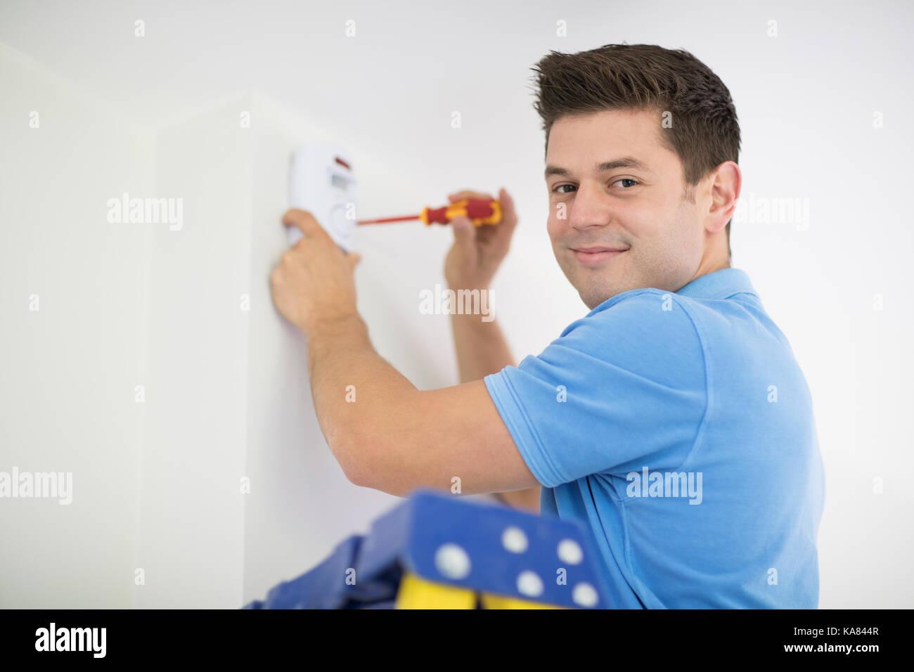 Security Consultant Fitting Burglar Alarm Sensor In Room - Stock Image