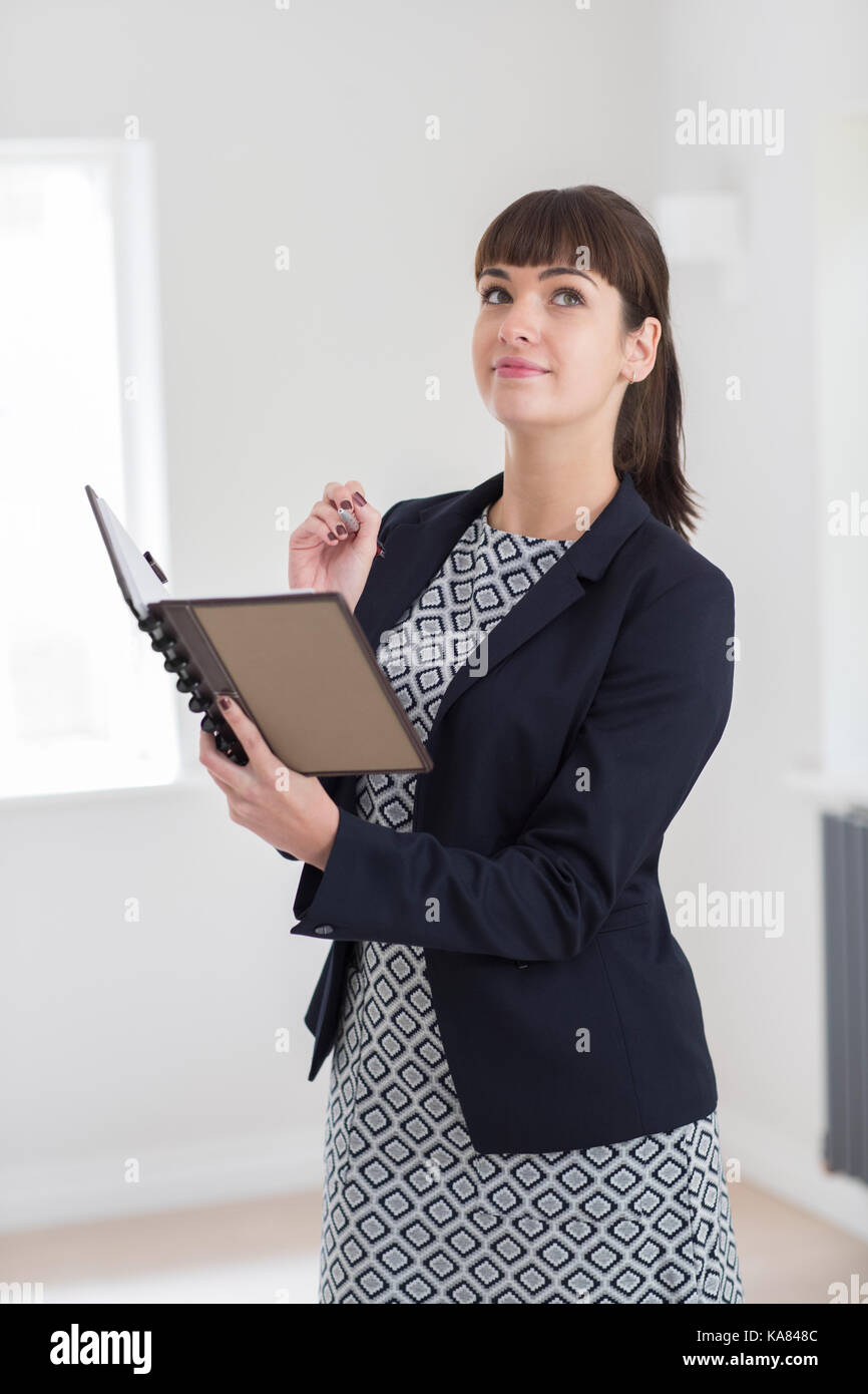 Female Estate Agent Looking Around Vacant Property For Valuation - Stock Image