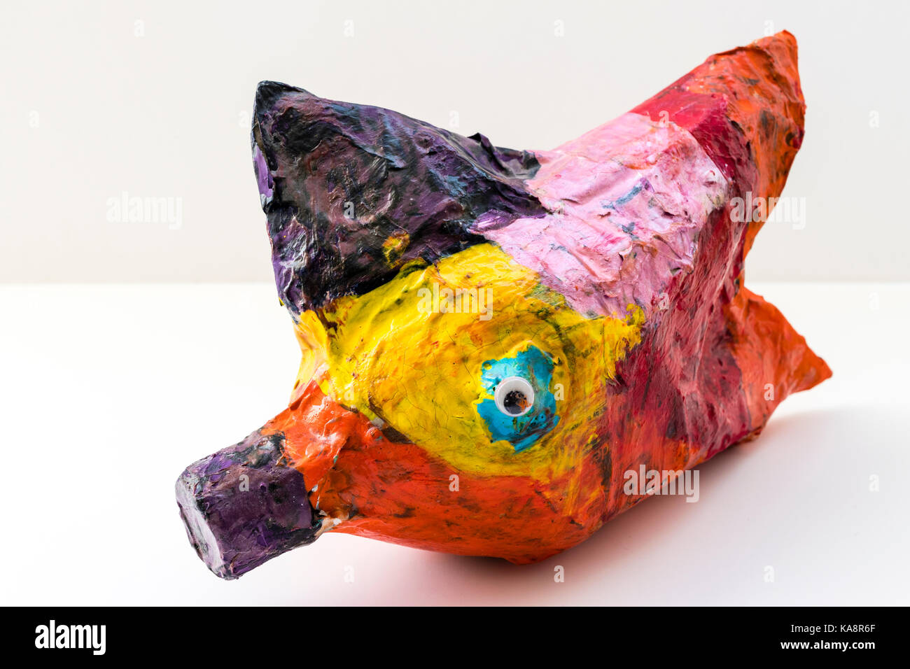 England. Child's creation, papier-mache fish multi-coloured on light grey background. - Stock Image