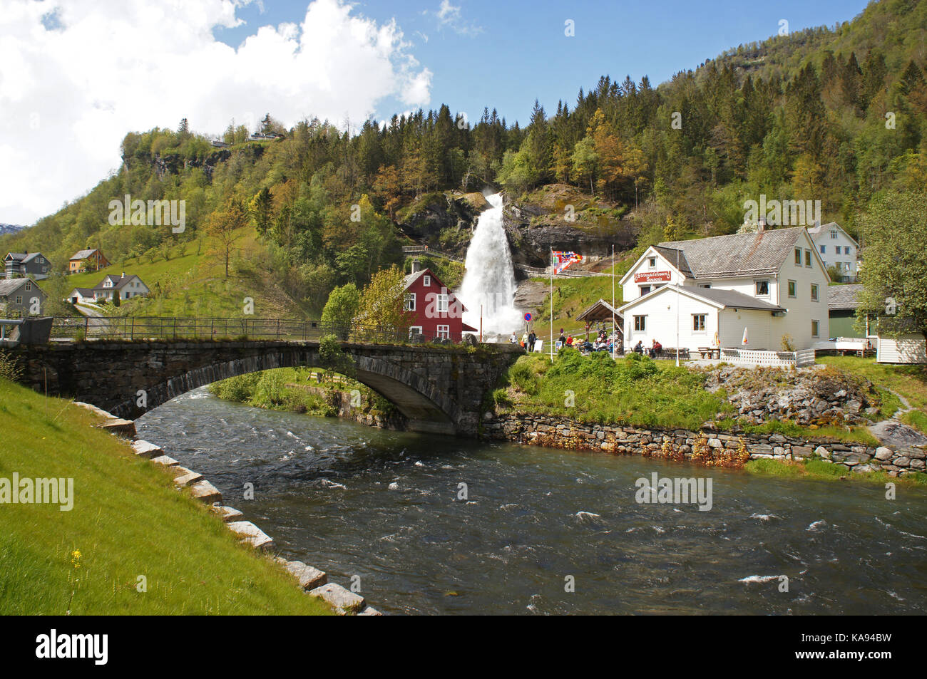 Steinsdalsfossen waterfall in the river of Steine, scenic landscape with cascade surounded by mountains and traditional - Stock Image