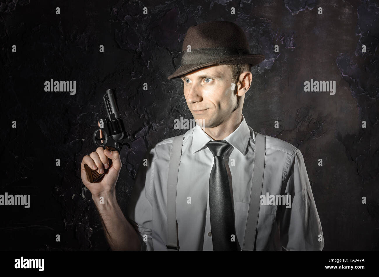 Black and white picture of a private detective with a gun in both hands. Agent in stylish hat. Man stays front to - Stock Image