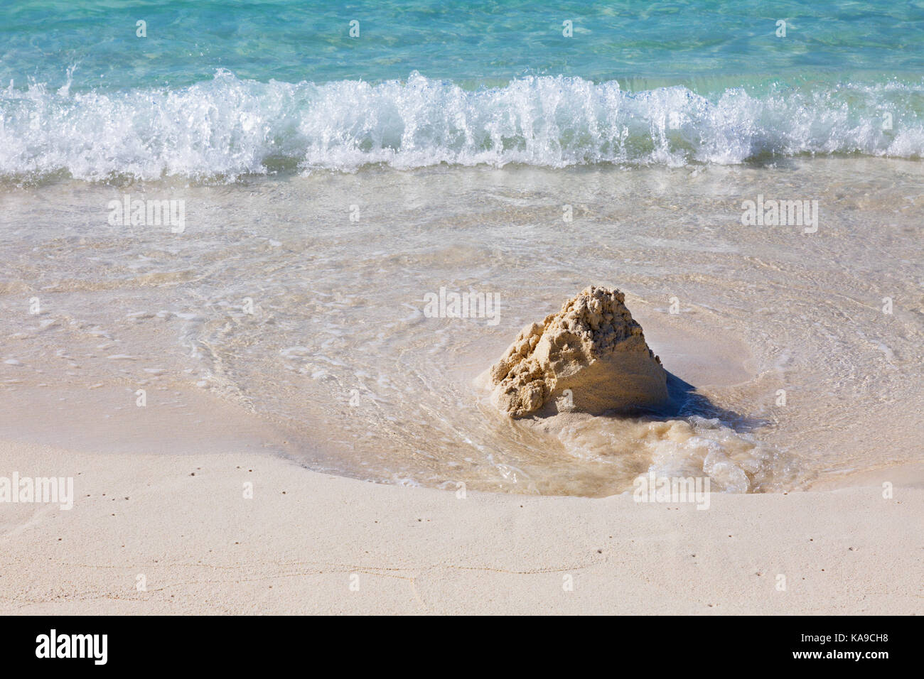 Sandcastle on the beach being washed away by the waves - concept of inevitability, time, temporary, - the Maldives, - Stock Image