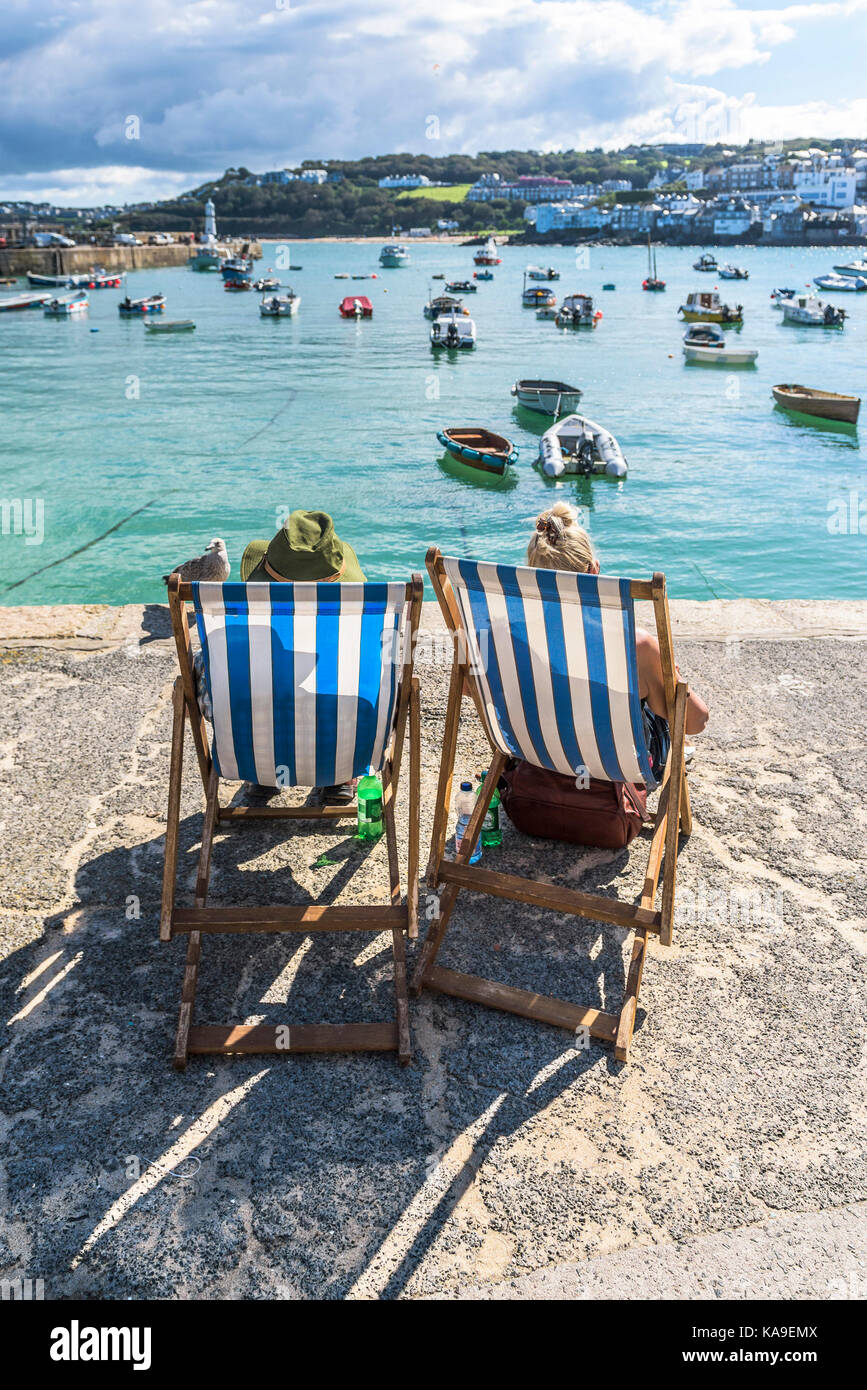 St Ives - holidaymakers relaxing in deckchairs on the quayside and enjoying the view over St Ives Harbour Cornwall. - Stock Image