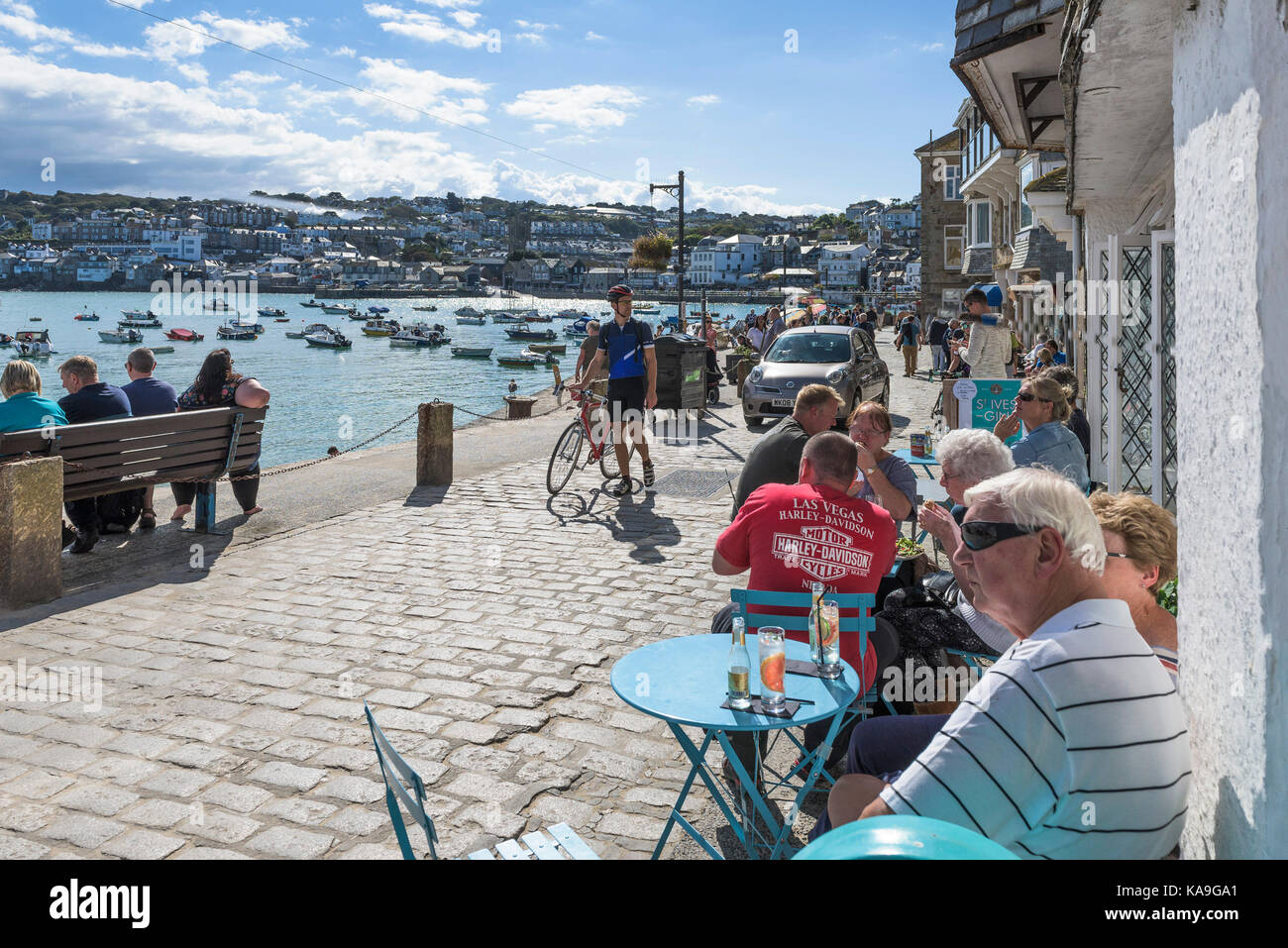 St Ives - holidaymakers relaxing on harbourside at St Ives Harbour in Cornwall. - Stock Image