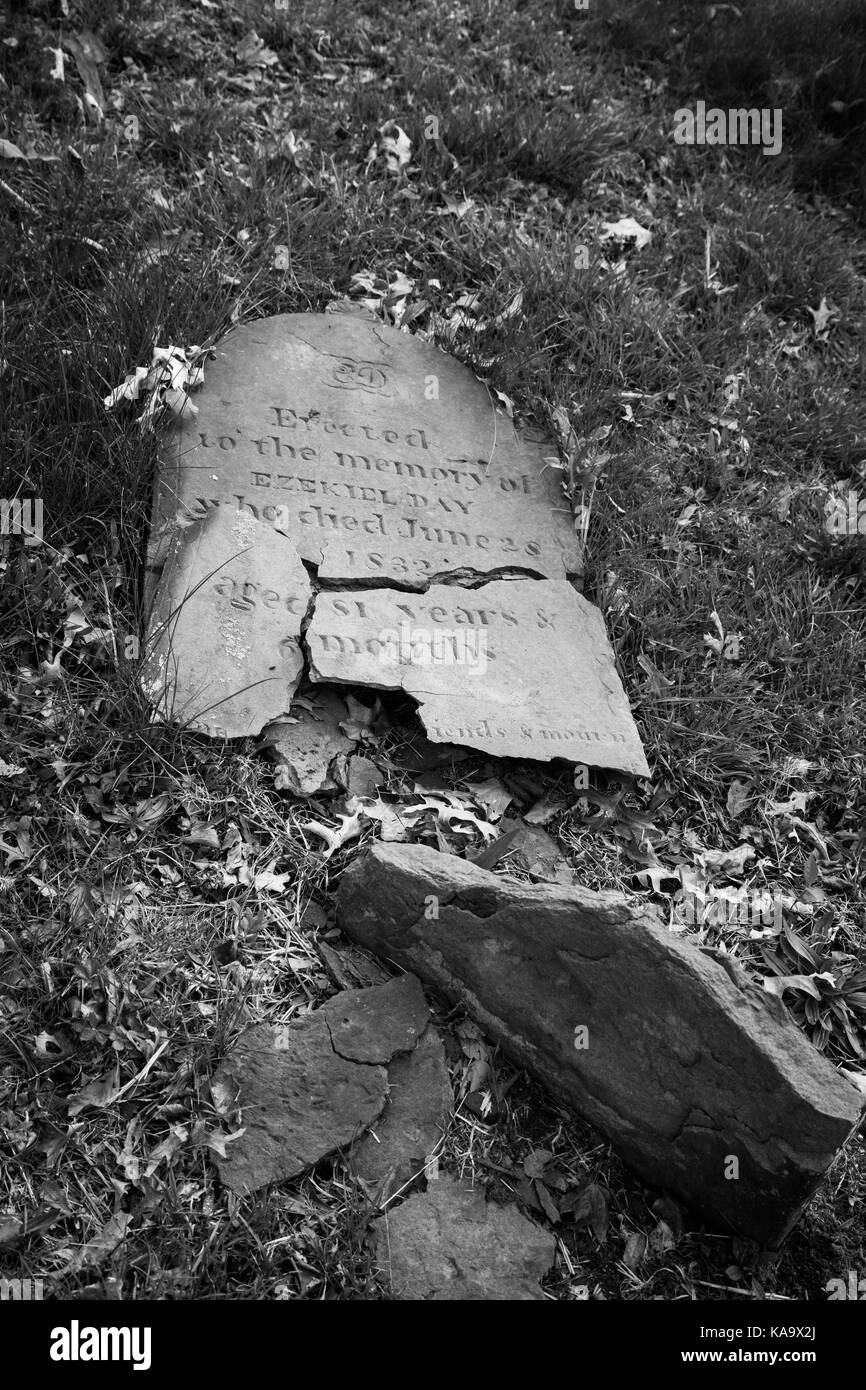RAHWAY, NEW JERSEY - April 28, 2017: An old tombstone has fallen apart and lays on the ground at Rahway Cemetery - Stock Image